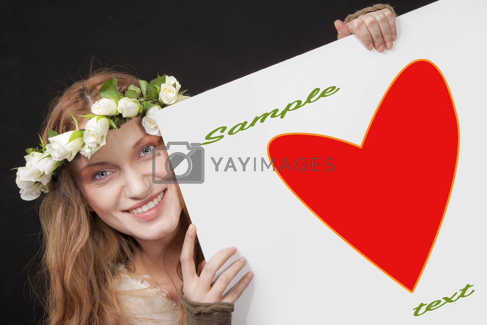 A smiling beautiful woman with white roses wreath in her long hair is holding a sign with red heart and a clipping path.