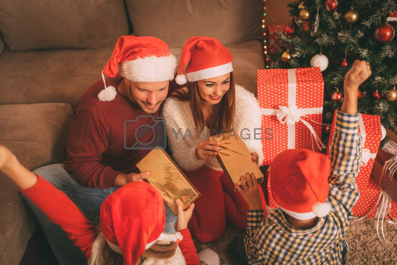 Beautiful happy family wearing santa hat and exchanging Christmas gifts at home. Selective focus.