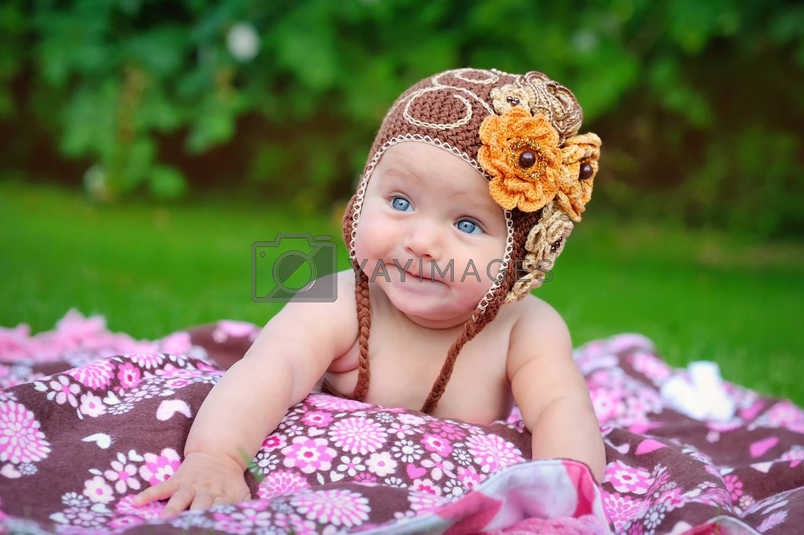 Cute baby crawling outdoors in brown knitted cap
