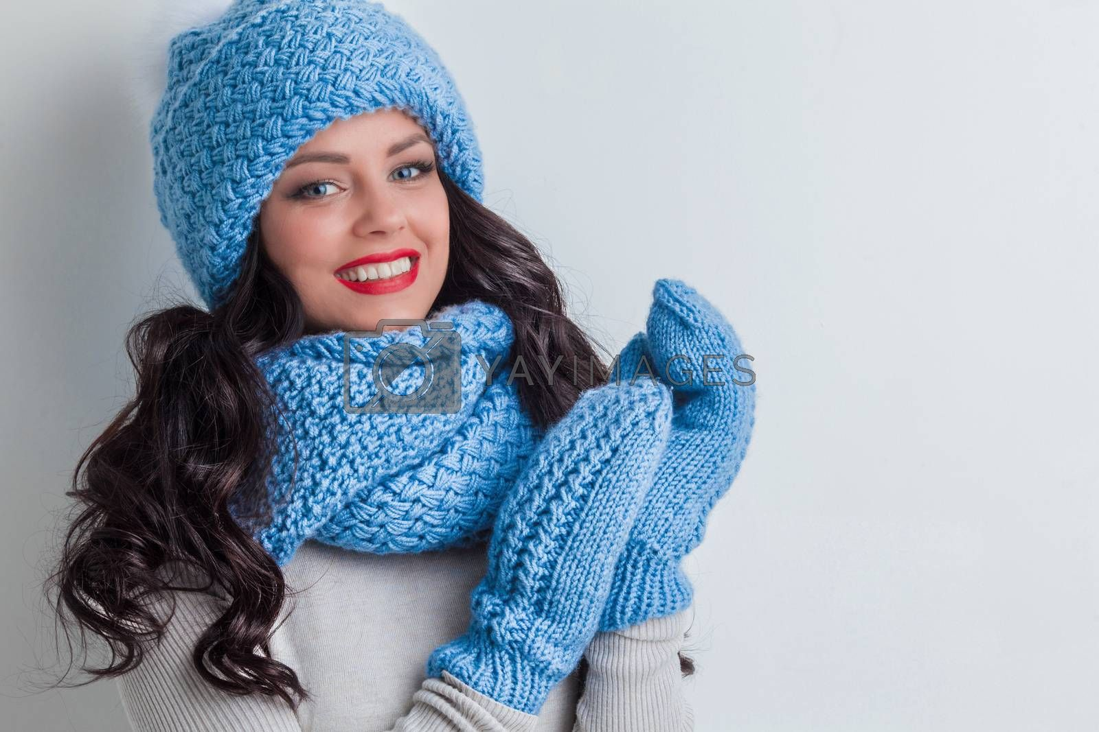 Smiling woman wearing blue winter hat, scarf and mittens