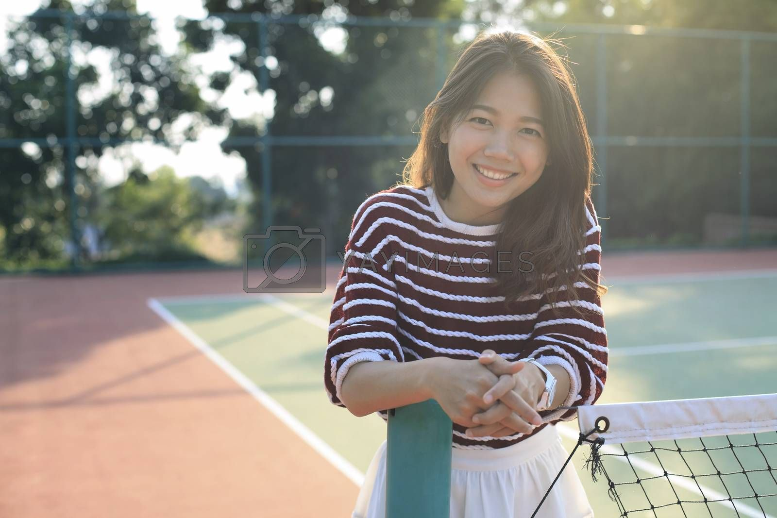 portrait of beautiful young asian woman waearing white clothes skirt in tennis course with happy face