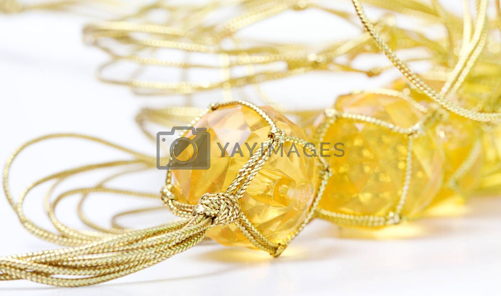 Royalty free image of necklace with cheap plastic gems with golden colored rope by nehru