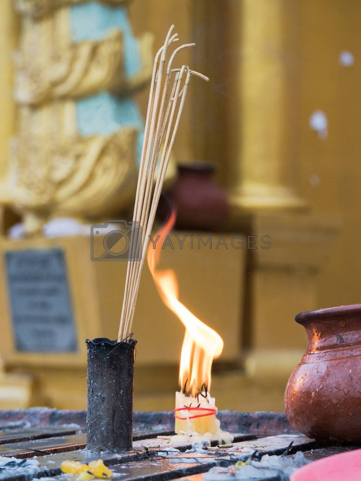 Joss sticks and a bundle of candles burning at dawn in front of a golden stupa at the Shwedagon Pagoda in Yangon, Myanmar. Shallow depth of field with the joss sticks in focus.