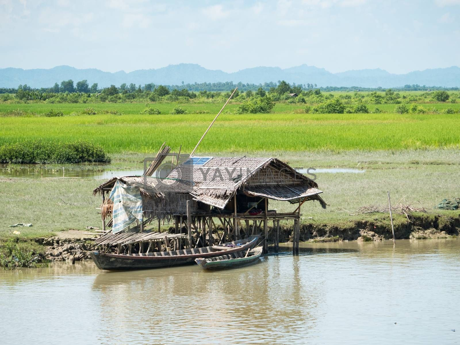Very simple, traditional farmhouse made from straw, but with a solar panel on the roof for electricity, along the Kaladan River in the Rakhine State of Myanmar.