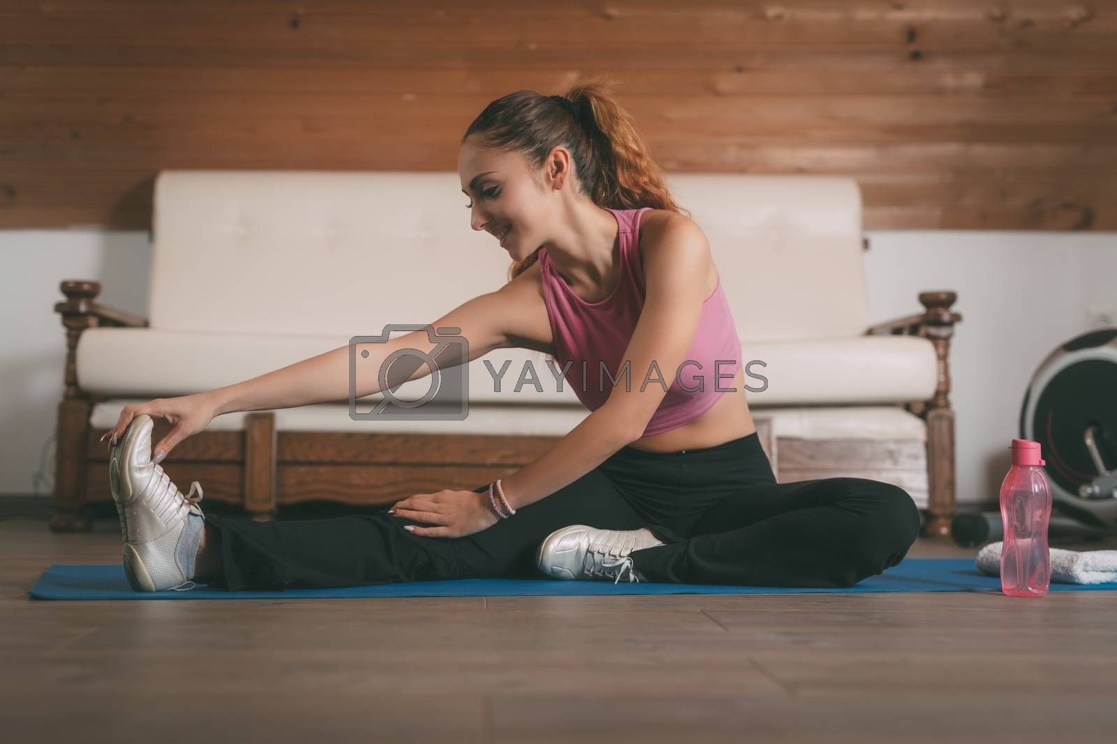 Beautiful young woman doing stretching exercises at the home.