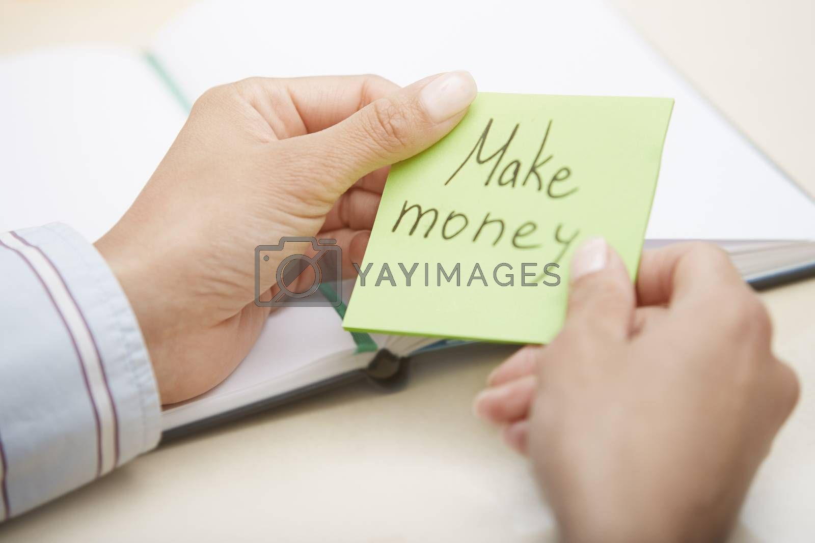 Hands of businessperson holding adhesive note with Make money text