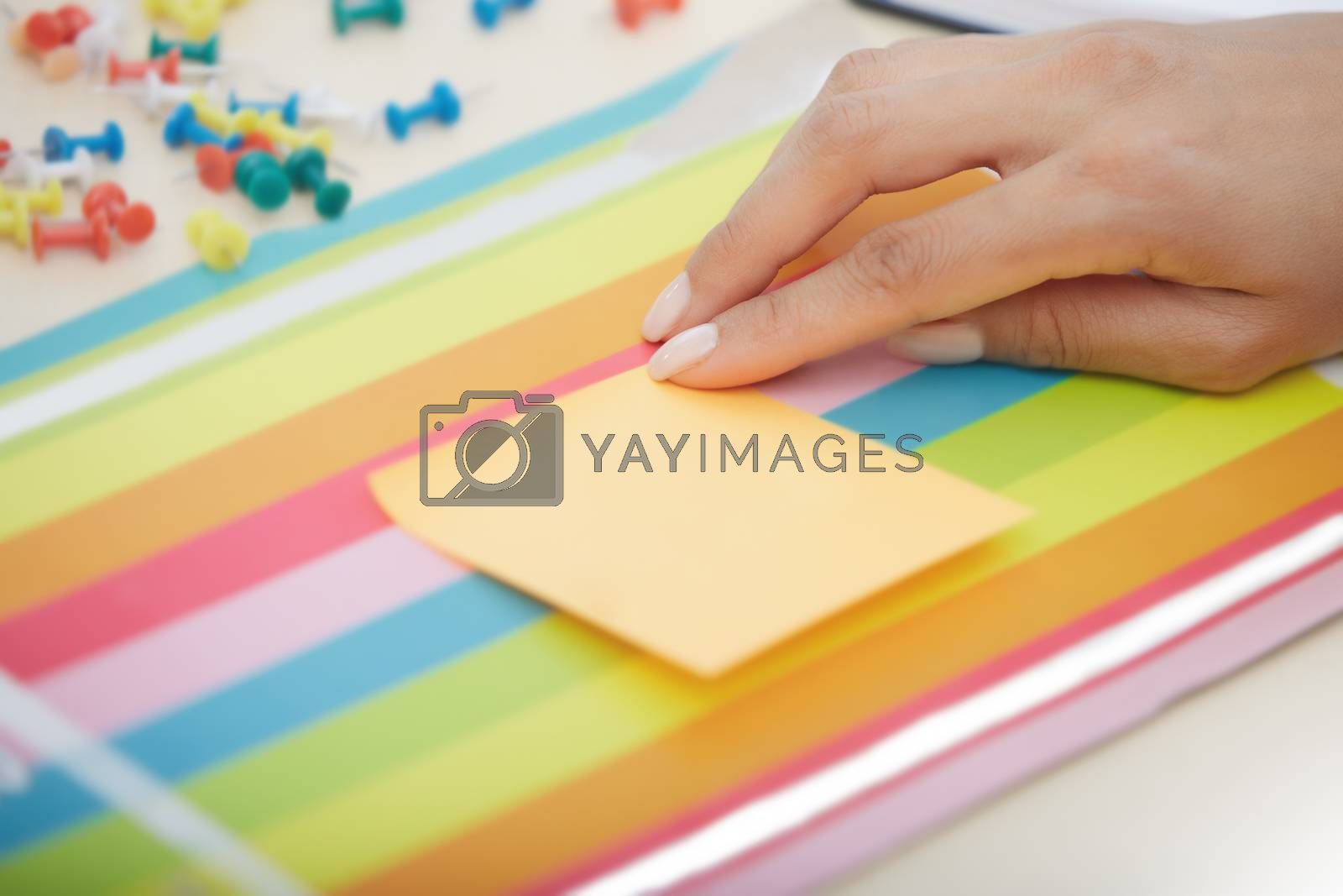 Businesswoman sticking adhesive note with empty space
