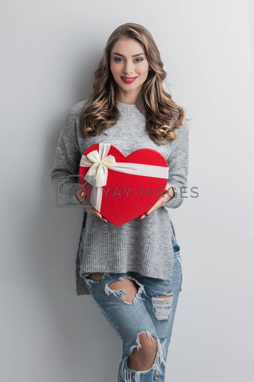 Young girl with red heart-shaped gift box on white background