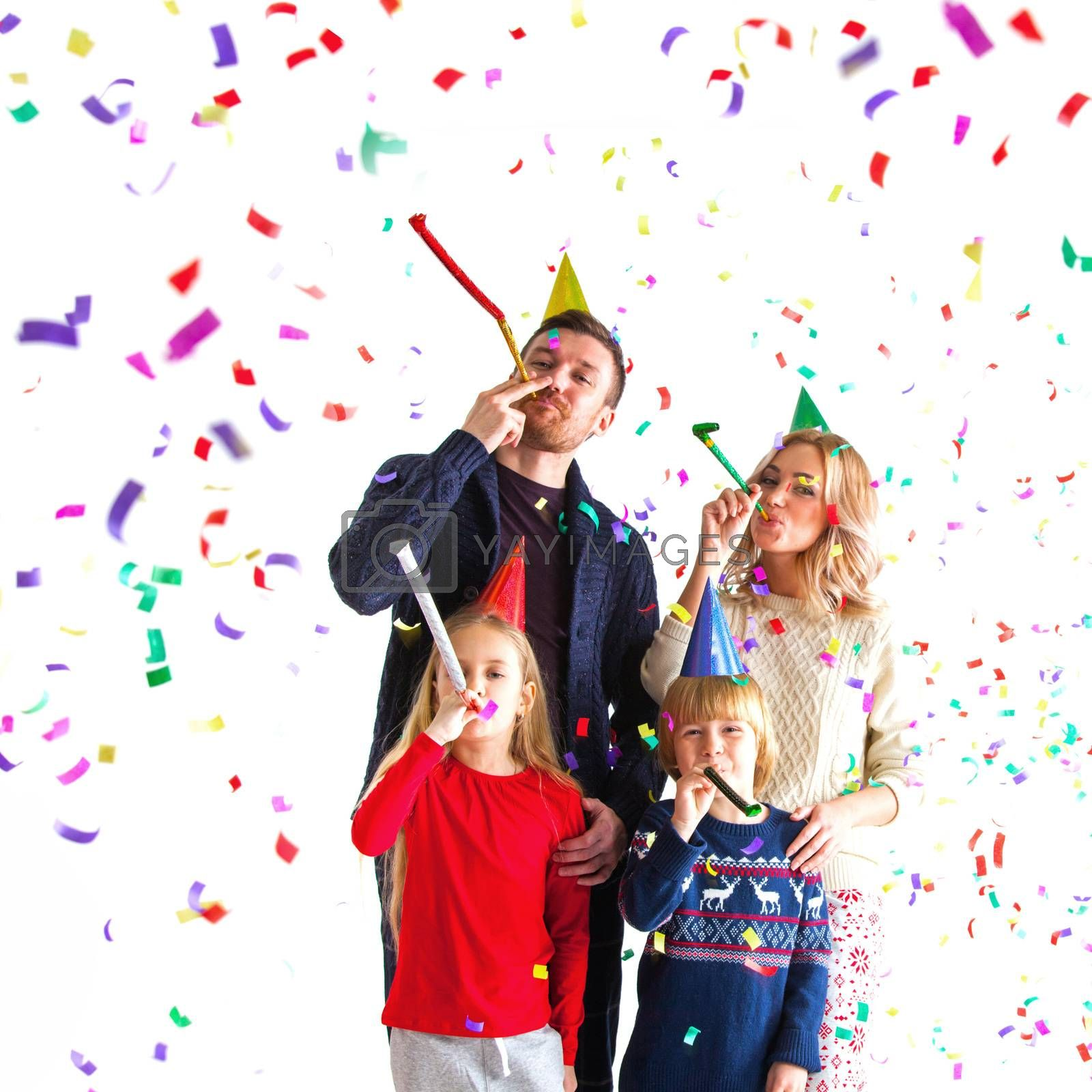 Family blowing party trumpets with confetti celebrating new year