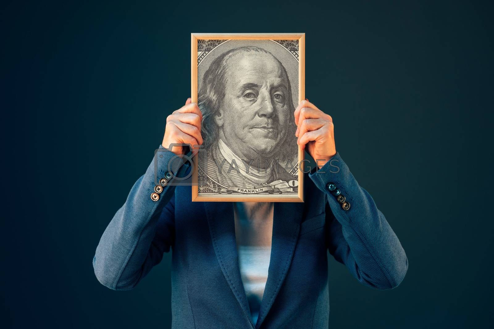 Businesswoman holding Benjamin Franklin 100 USA dollar portrait in front of her face