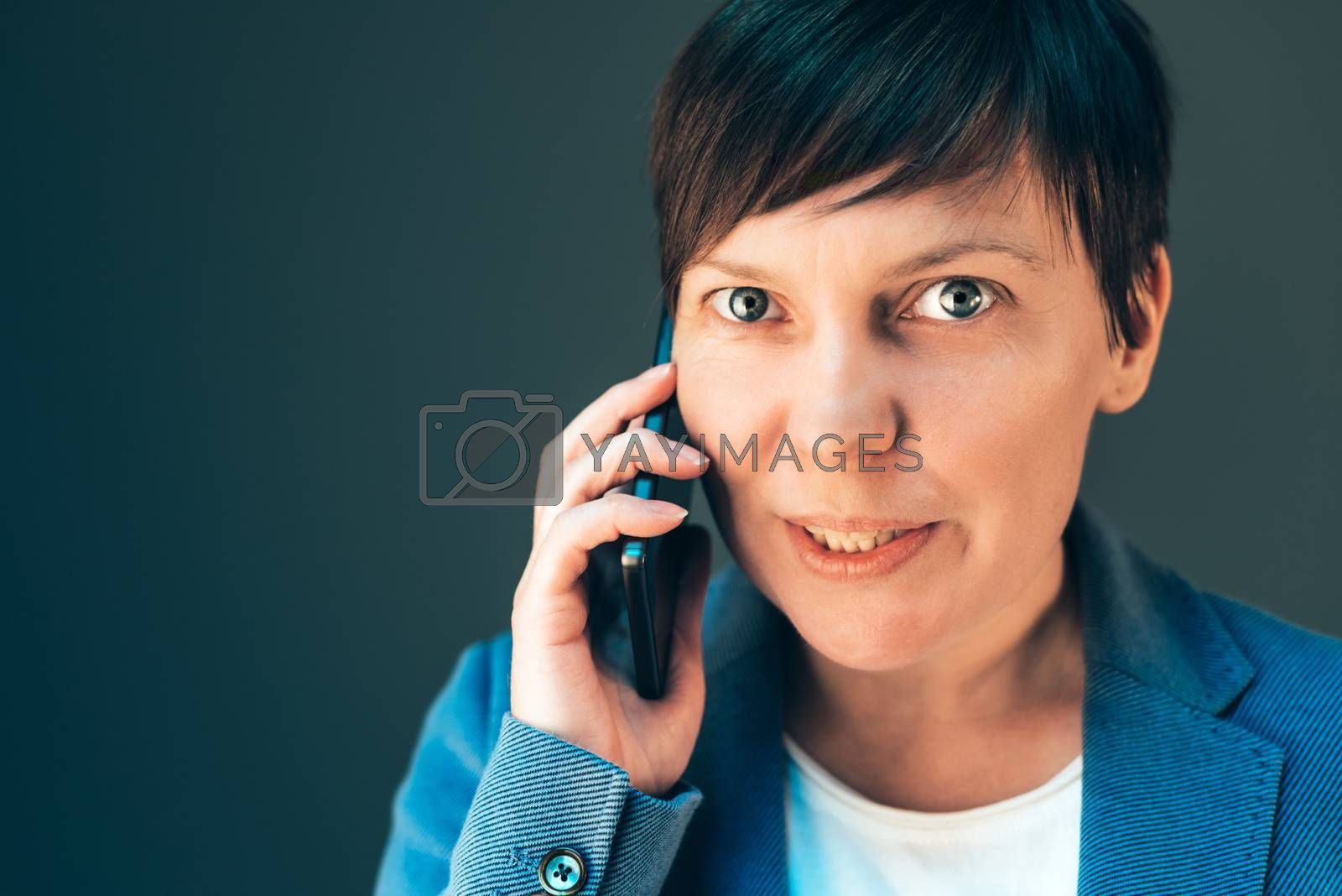 Beautiful businesswoman talking on smartphone, female in business conversation