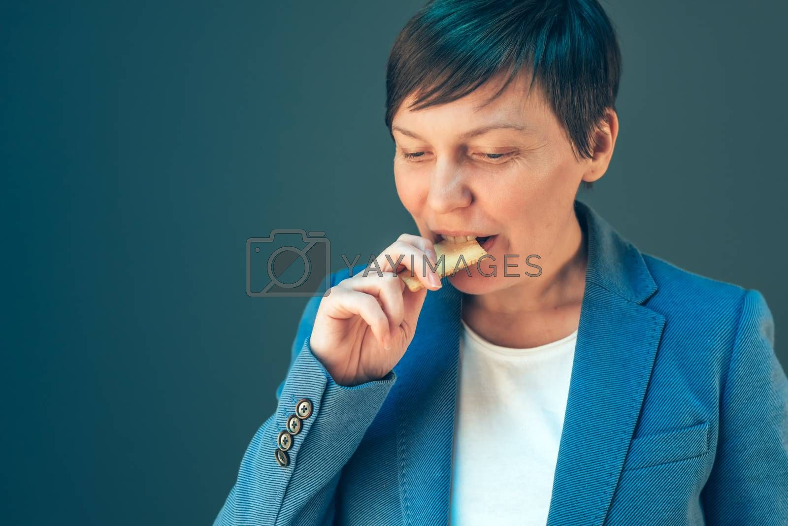 Businesswoman eating cookie on a break, dieting and fast snack on the job