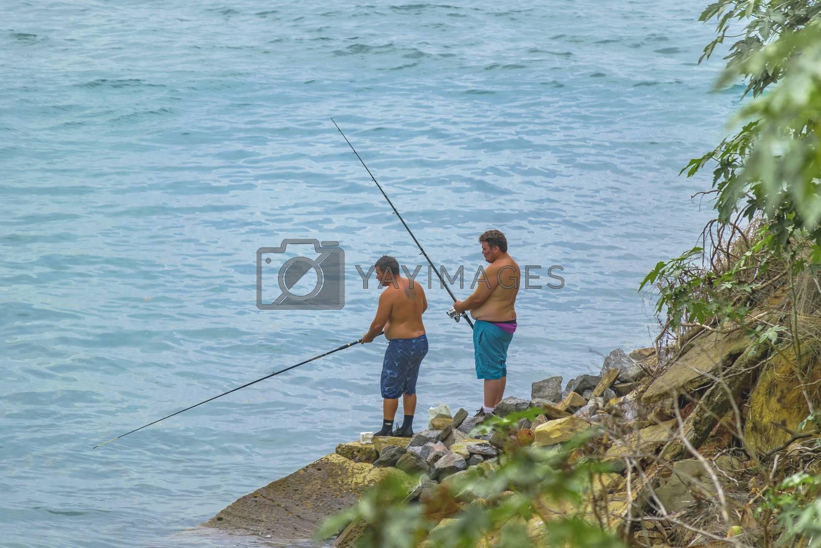 TIBAU DO SUL, BRAZIL - JANUARY - 2016 - Two adult fisherman fishing at shore of ocean in Tibau do Sul, Brazil