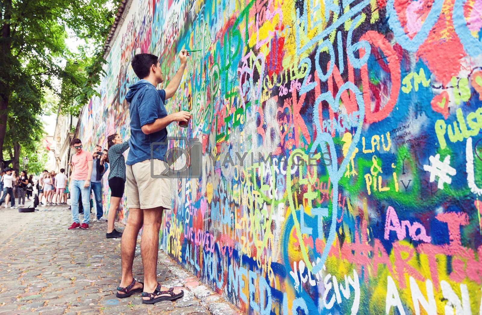 PRAGUE, CZECH REPUBLIC - JUNE 27, 2016: Young man painting the famous Lennon graffiti wall in old town of Prague, Czech Republic