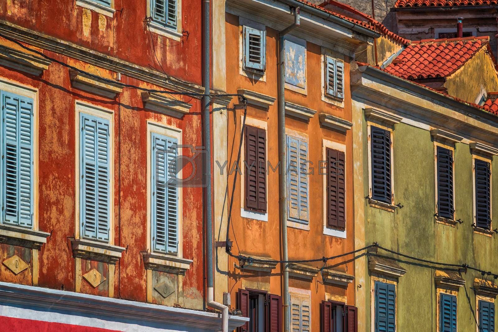 Weathered colorful mediterranean town building facades on bright sunny summer day