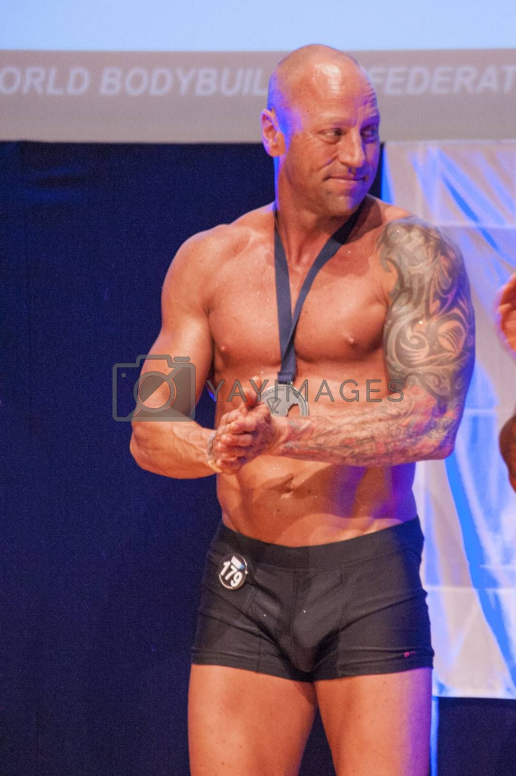 MAASTRICHT, THE NETHERLANDS - OCTOBER 25, 2015: Male physique model Erik Stobbe celebrates his victory on stage at the World Grandprix Bodybuilding and Fitness of the WBBF-WFF on October 25, 2015 at the MECC Theatre in Maastricht, the Netherlands.