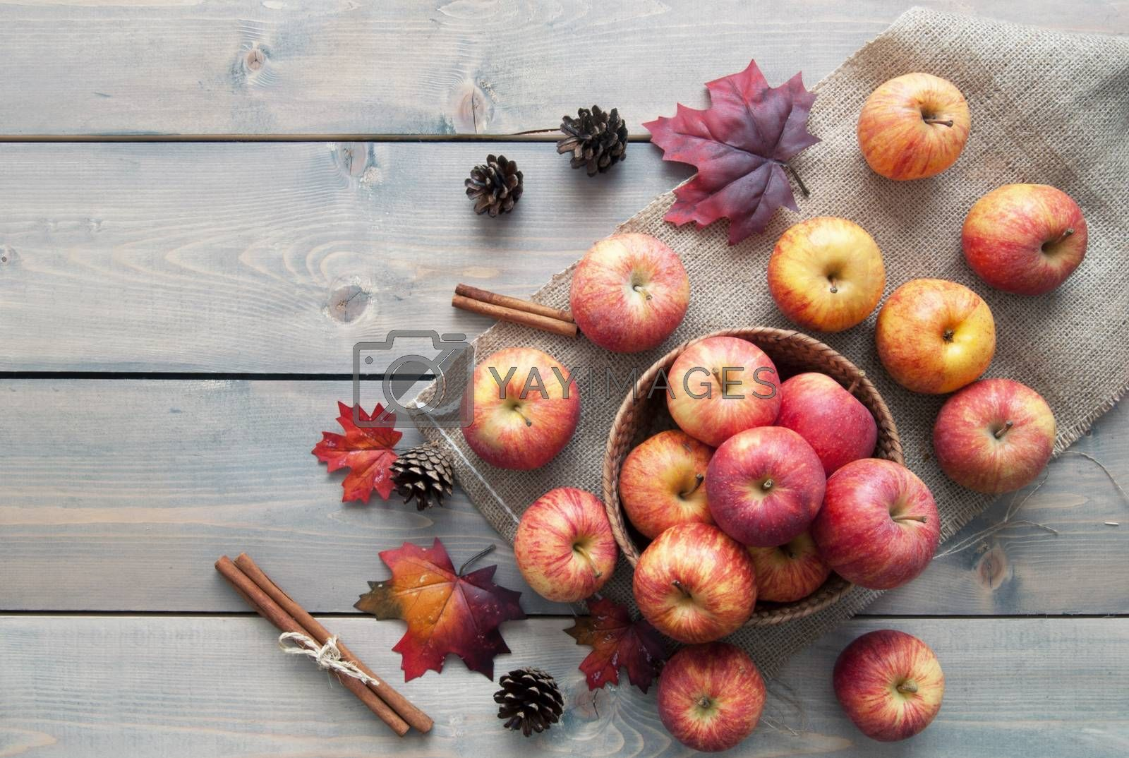 Autumn leaves with apples over a wooden background