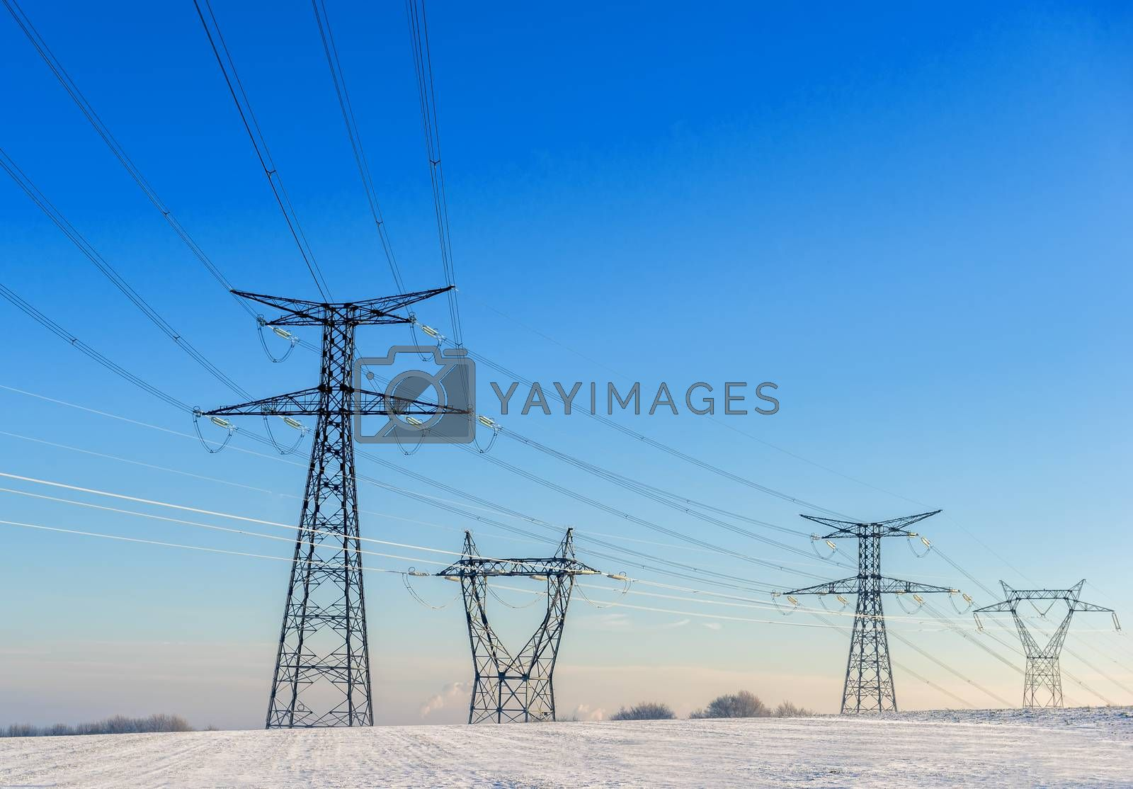 power lines in a snowy landscape on blue sky