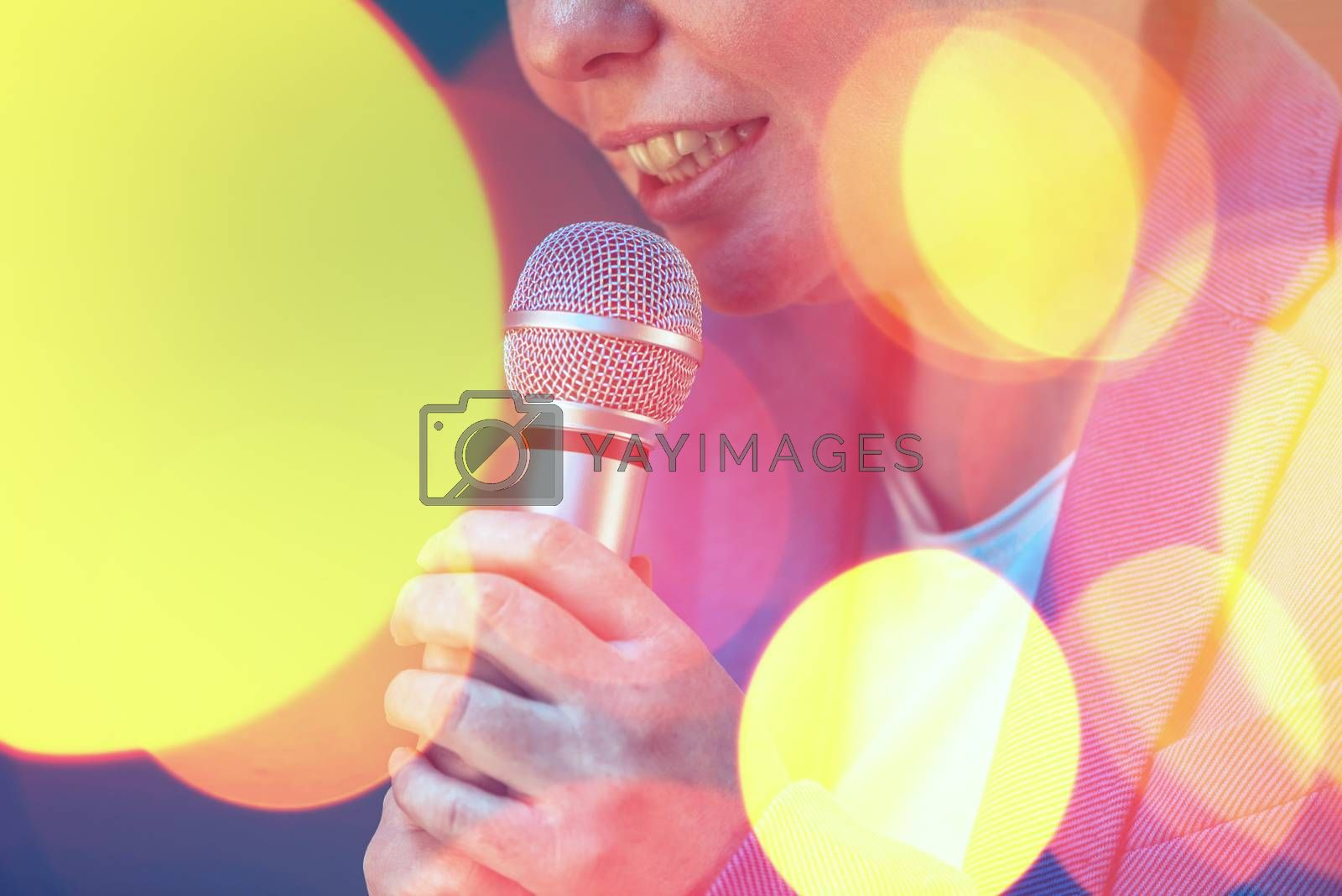 Royalty free image of Beautiful woman singing karaoke song with microphone by stevanovicigor