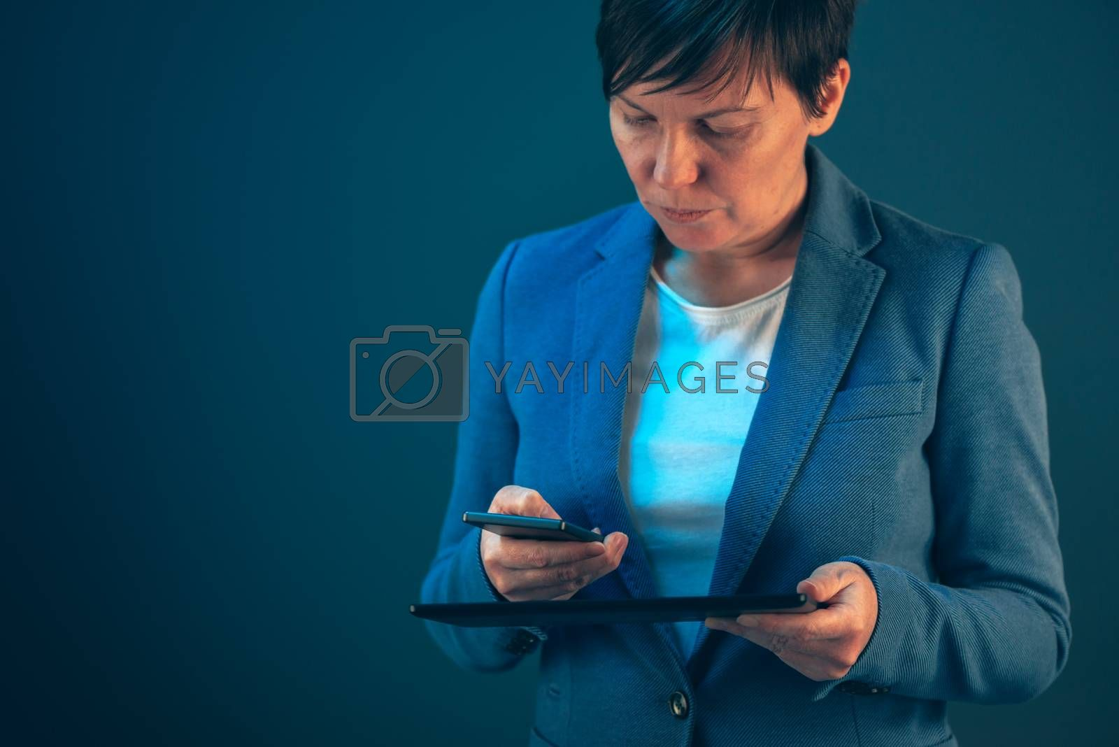 Smartphone and tablet data synchronization, businesswoman syncing files and documents on wireless electronic devices at business office