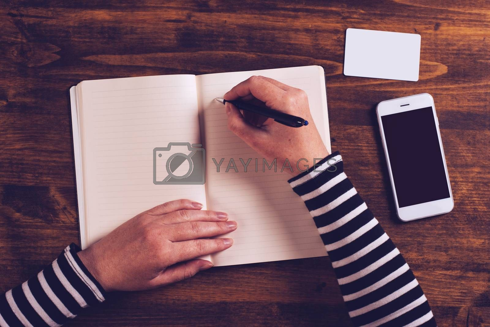 Woman writing contact list from mobile phone into her business agenda notebook for backup, top view of office desktop