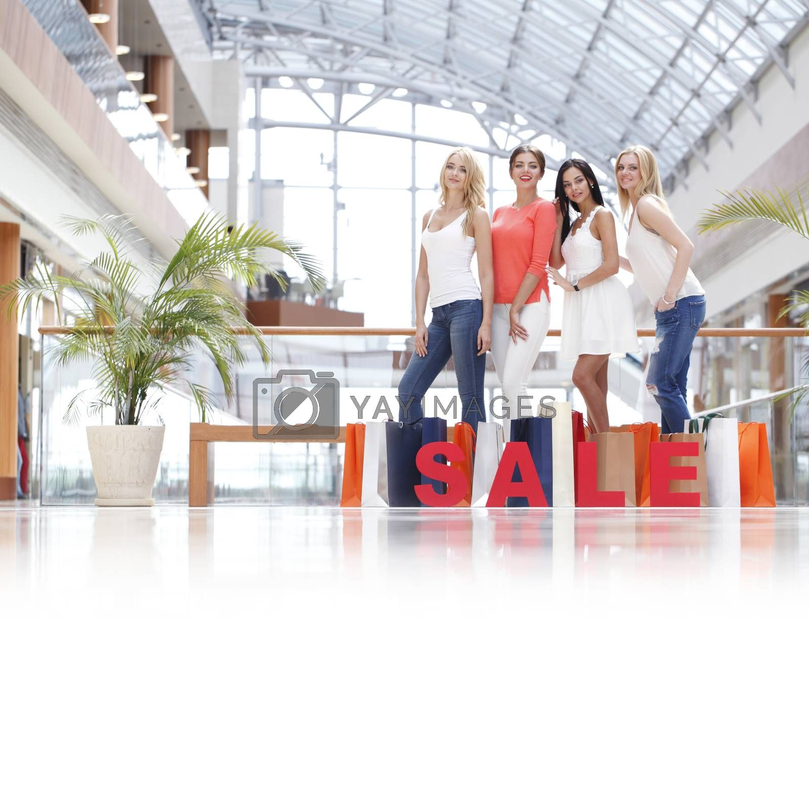 Women with red sale letters in mall, shopping concept
