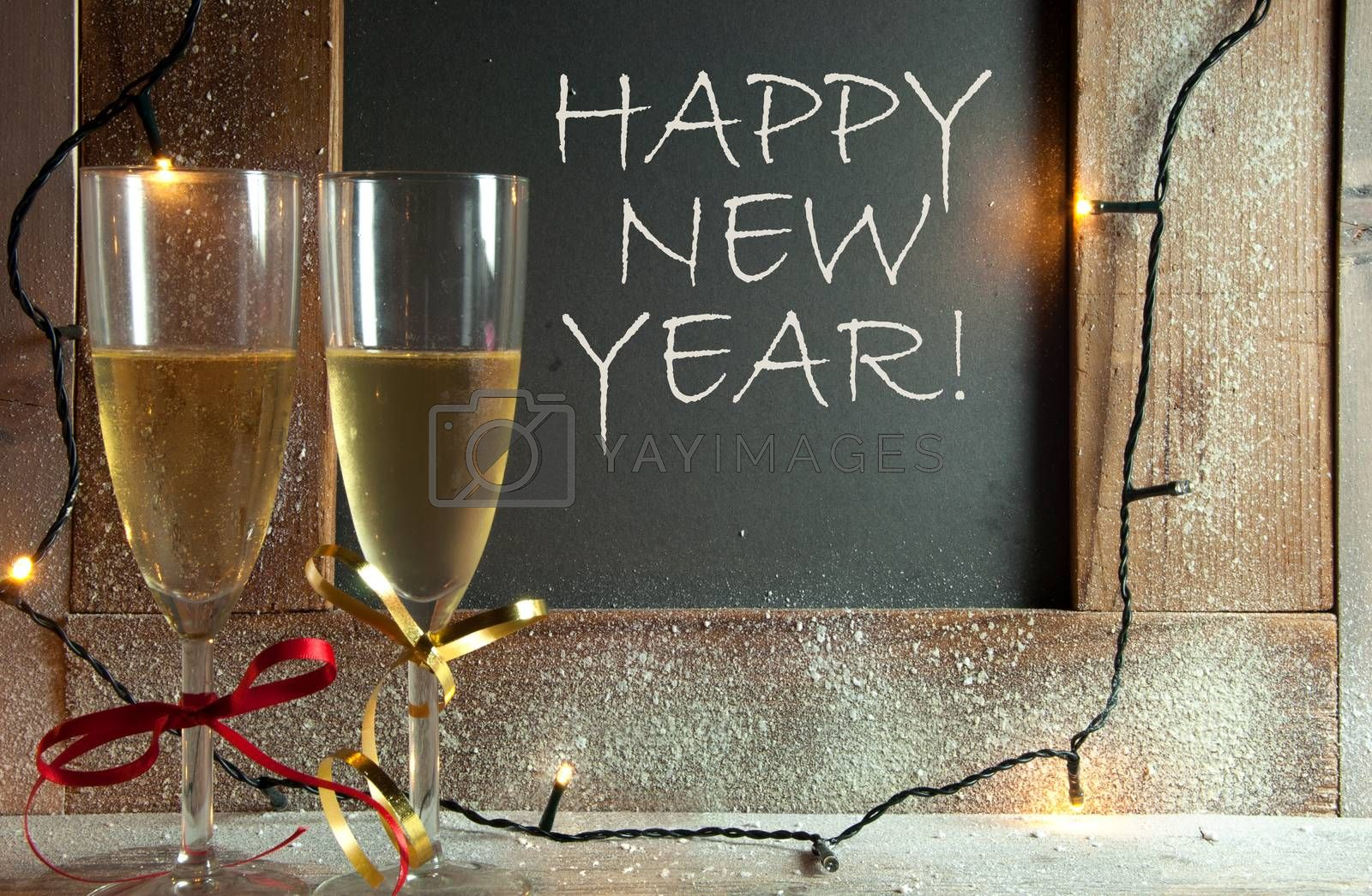 Two champagne glasses next to chalkboard with happy new year greeting