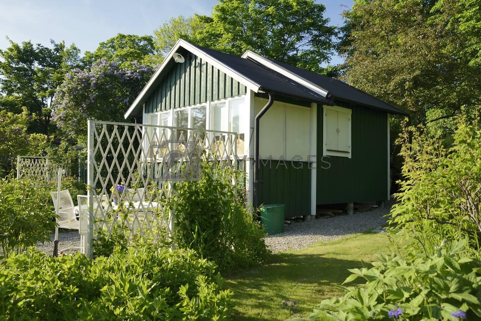 Idyllic green cottage in botanical garden.