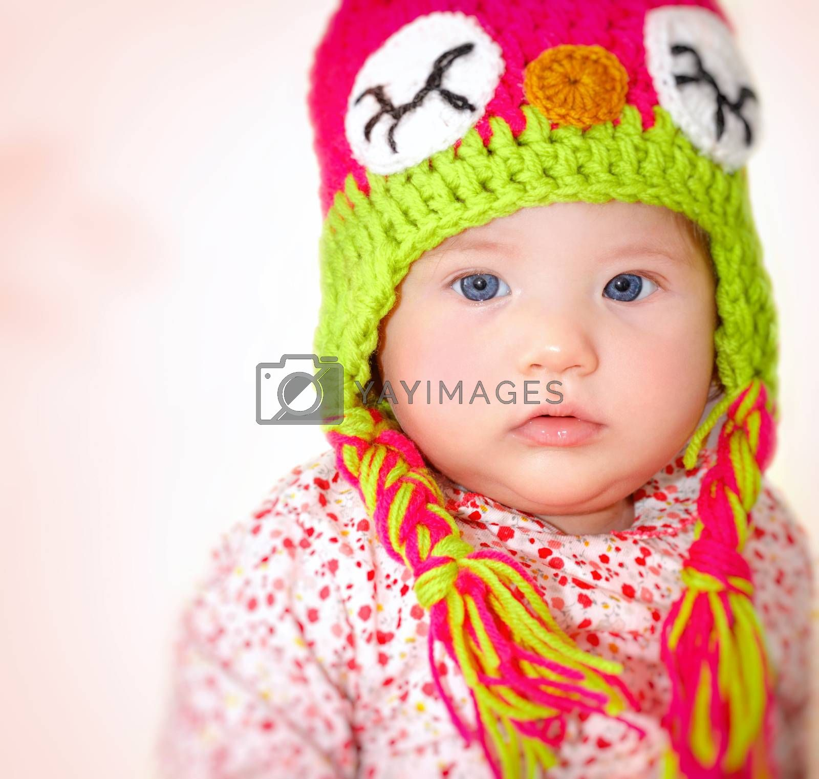 Closeup portrait of adorable child wearing beautiful colorful hat over pink background, cool winter style for little girls