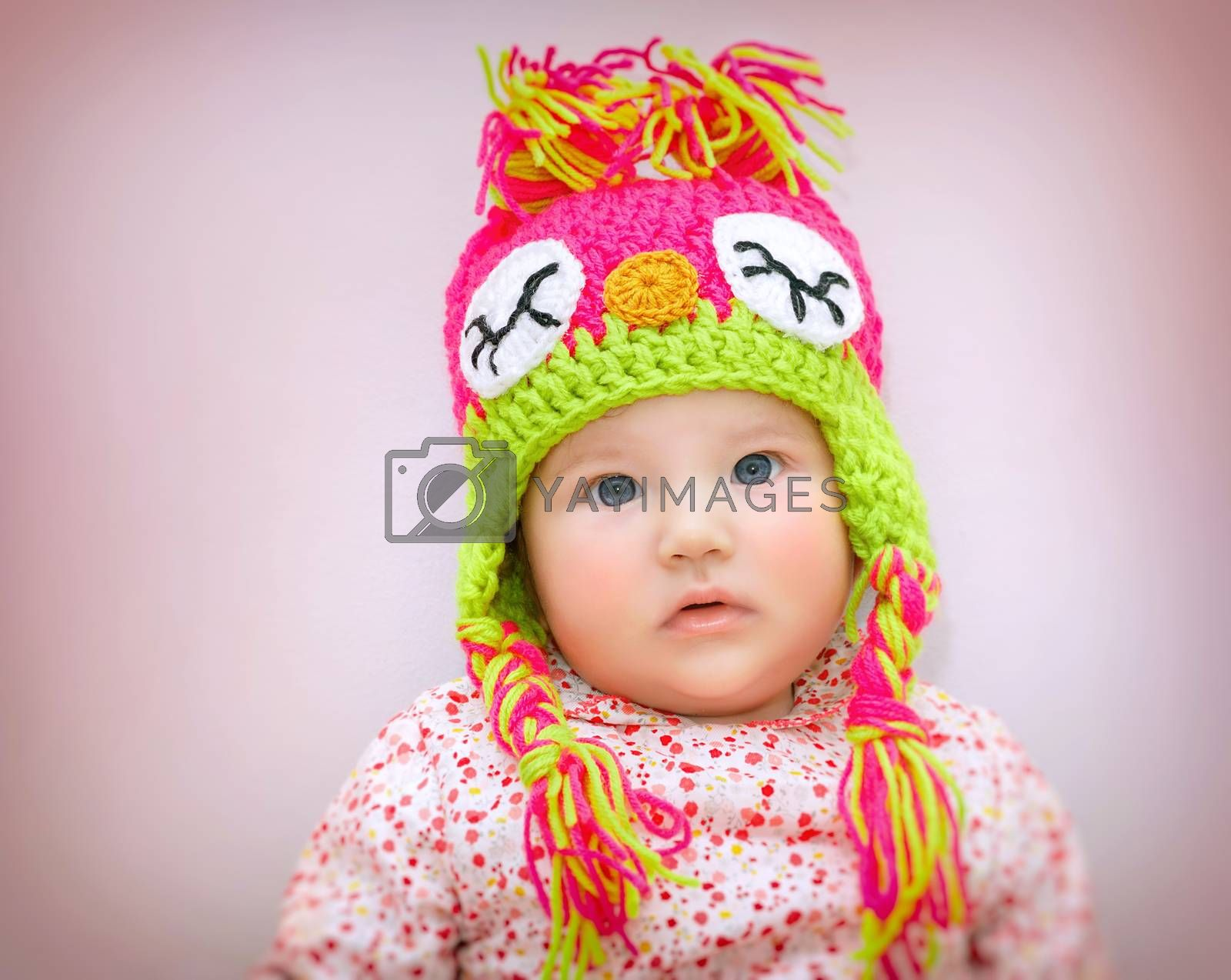 Portrait of beautiful little baby girl wearing stylish warm colorful knitted hat over pink background, winter children's fashion