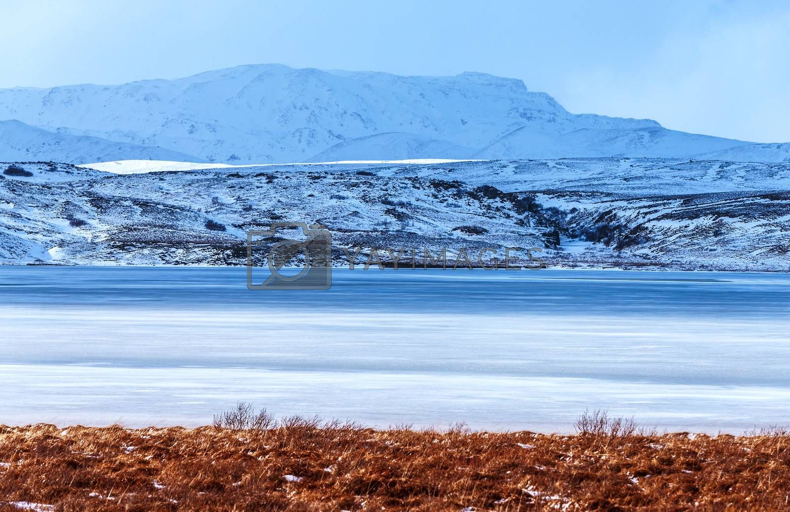 Beautiful winter landscape, big frozen lake near high mountains covered with snow, amazing nature of Iceland