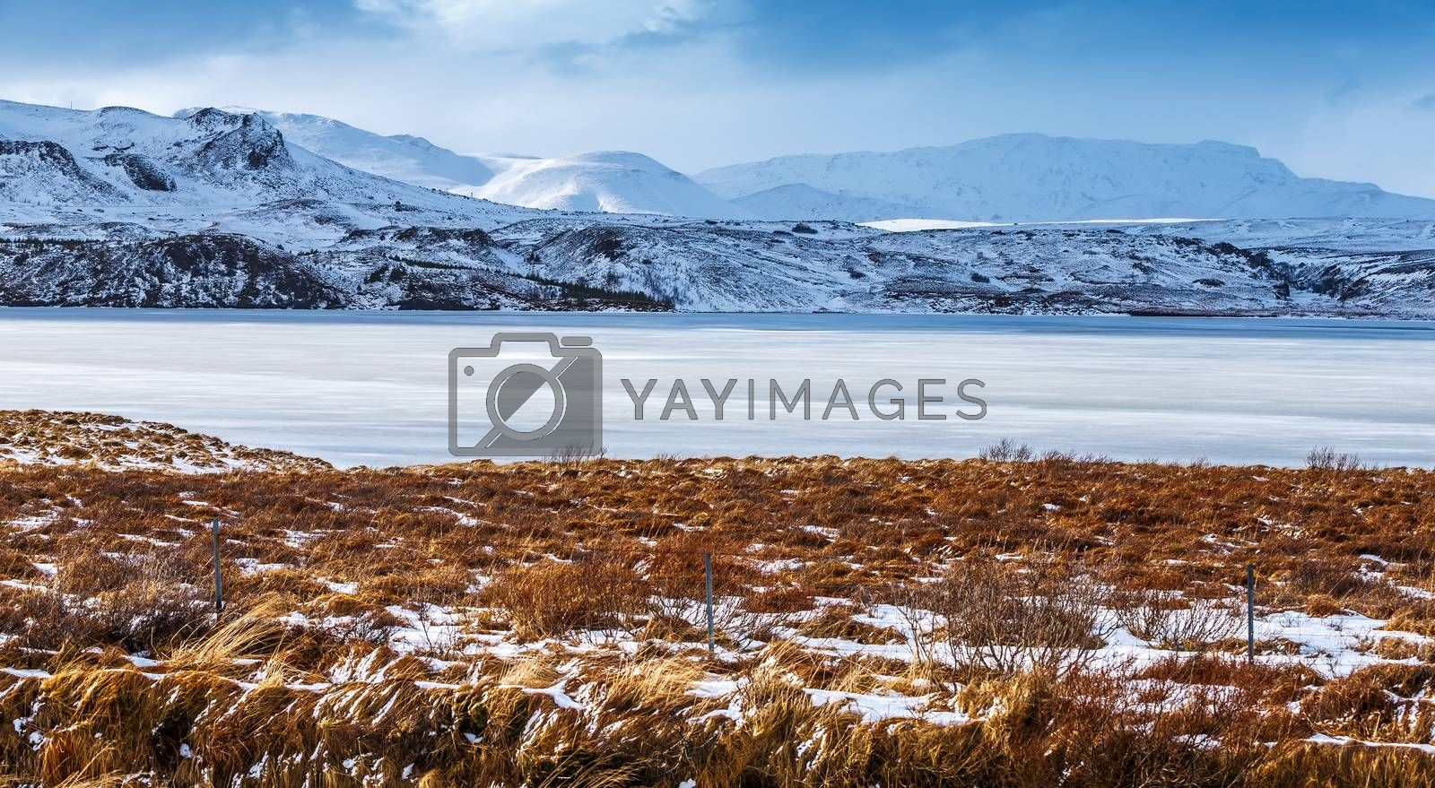 Beautiful winter landscape, panoramic view on the frozen lake and mountains covered with snow in the distance, amazing nature of Iceland