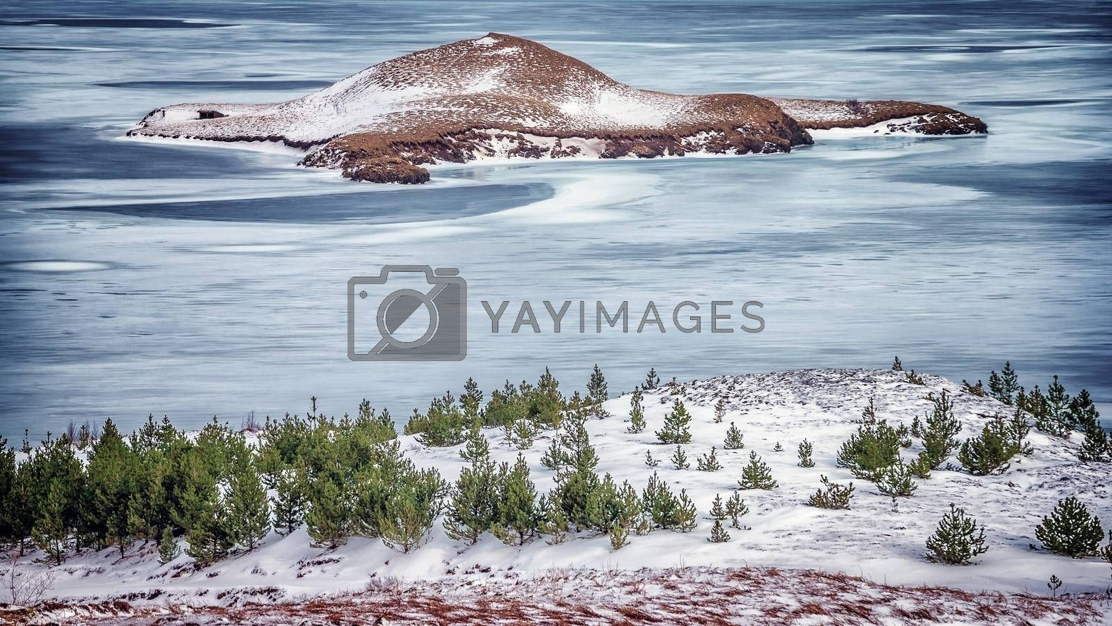 Beautiful winter landscape, frozen lake with little island in the center, amazing view on gorgeous nature, Iceland