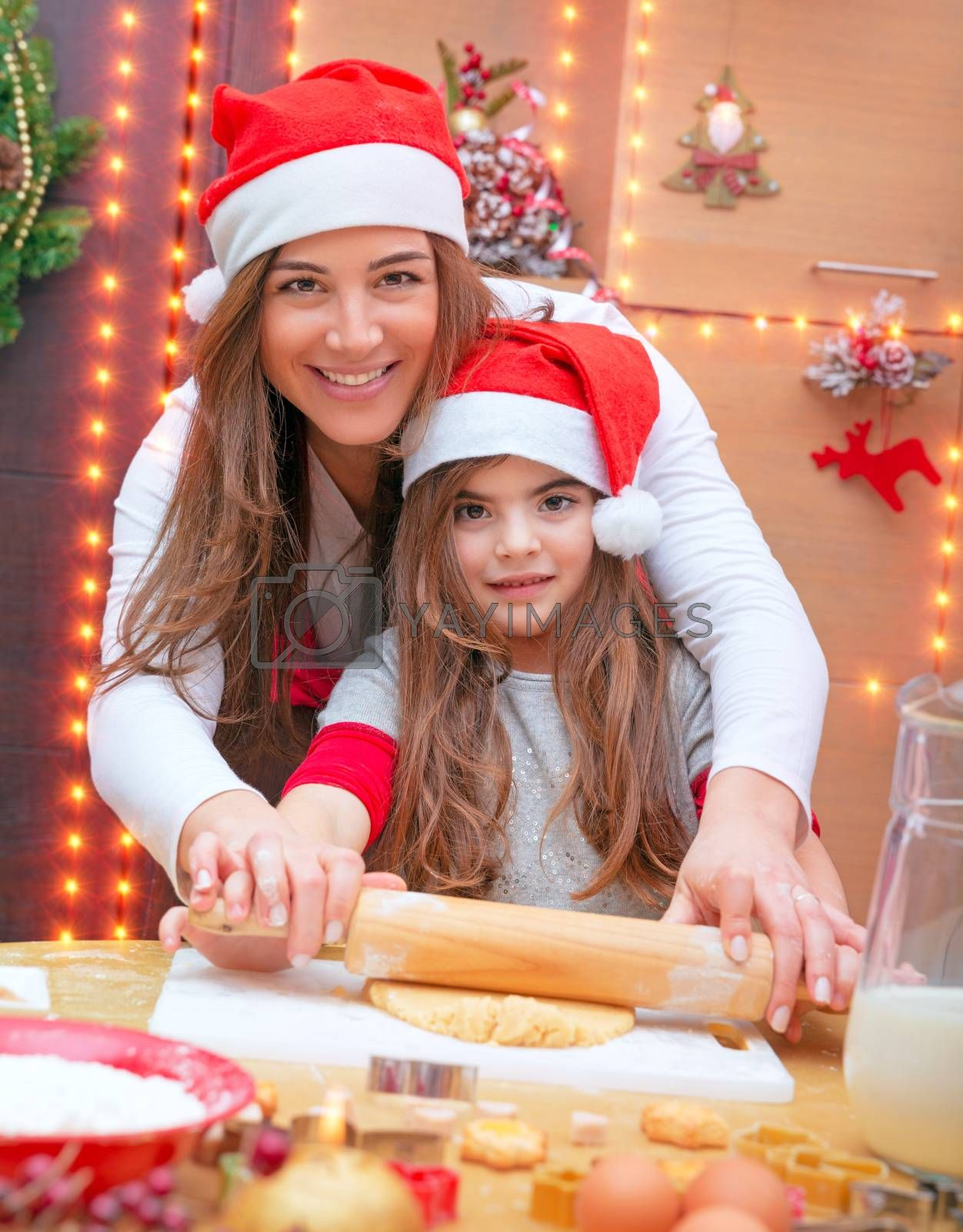 Happy family making Christmas cookies, mother and little daughter molding the dough at home, traditional preparation for Xmas holidays