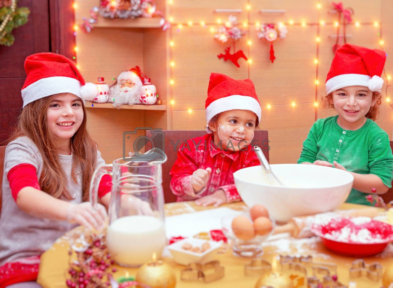 Happy children making Christmas cookies at home, three cute little kids wearing red Santa hats preparing festive tasty sweets, traditional celebration of winter holidays