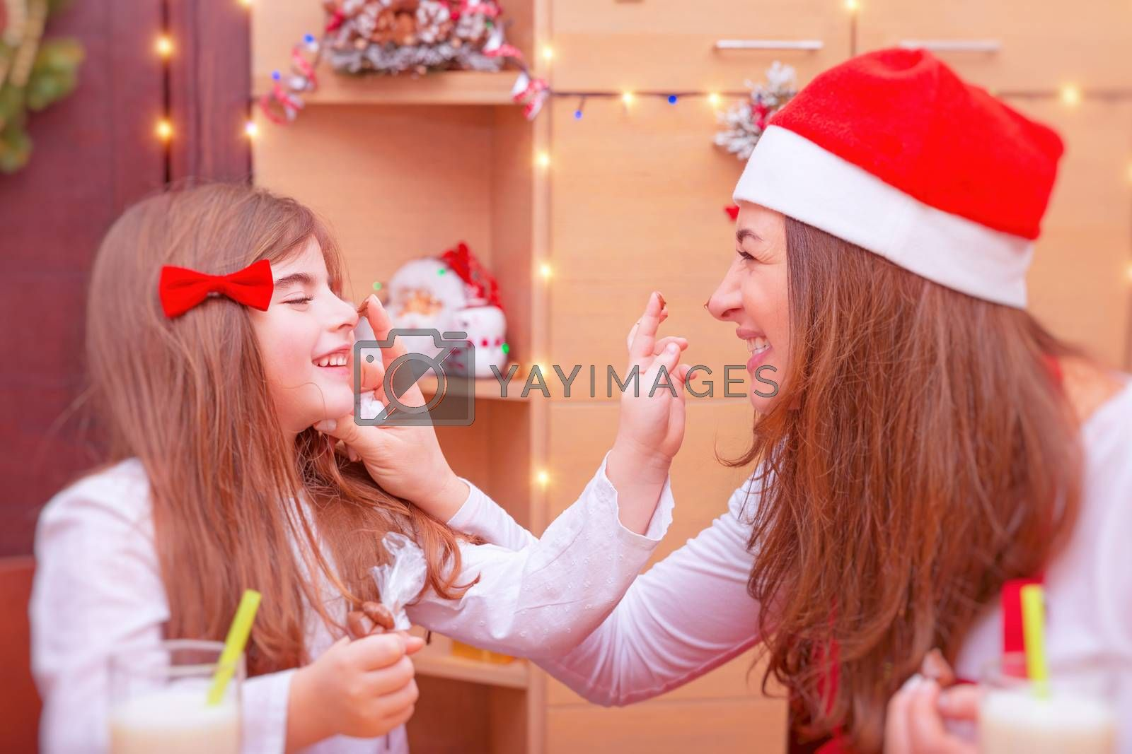 Mother with cute little daughter having fun at home in Christmas eve, smudge each other by chocolate, spending happy time with family on winter holidays