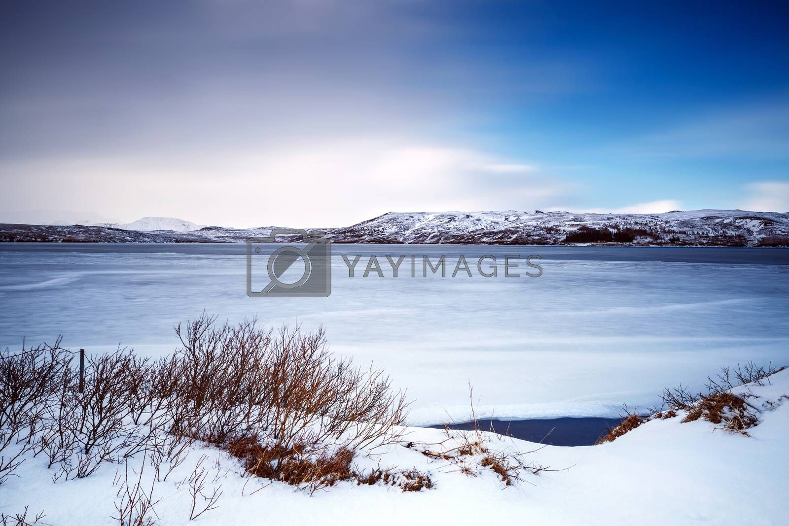 Beautiful winter landscape, big frozen lake near mountains covered with snow, amazing nature of Iceland