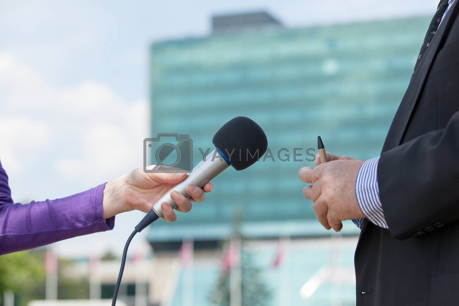 Female reporter interviewing business person, corporate building in background