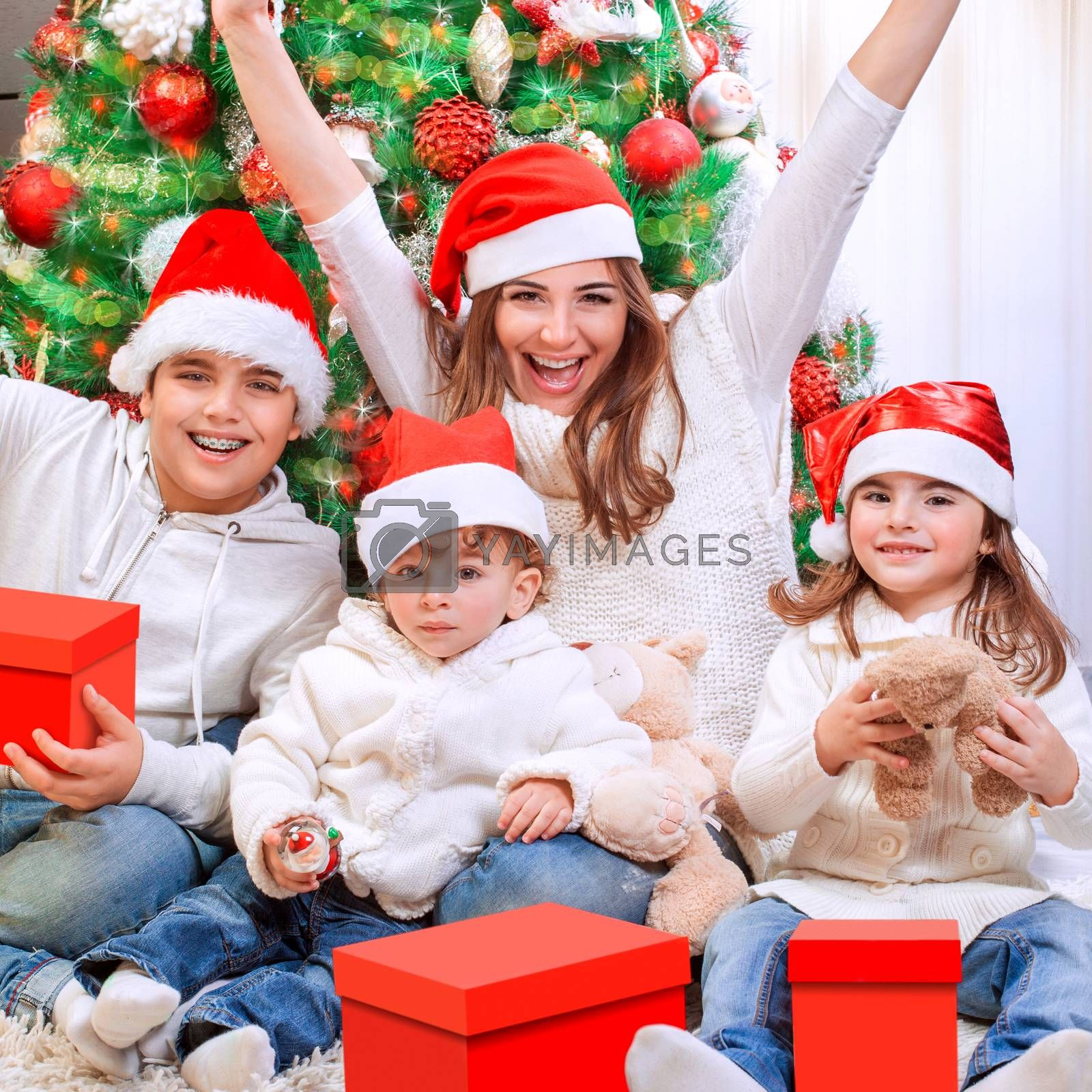 Portrait of happy mother with three cheerful kids enjoying gifts receiving from Santa Claus, having fun near Christmas tree