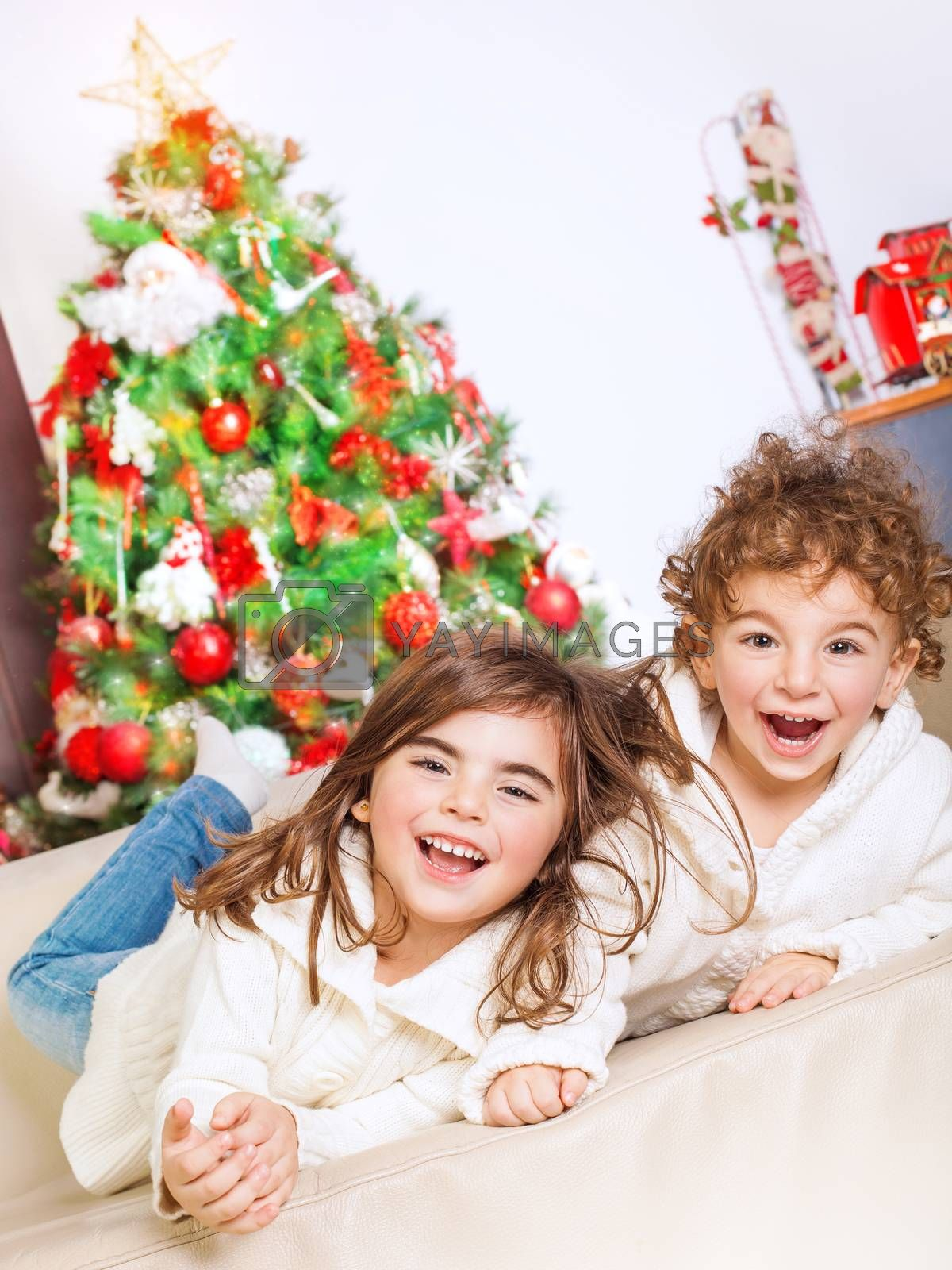 Two happy kids lying down on sofa near beautiful decorated Christmas tree and laughing, cheerful family spending winter holidays at home