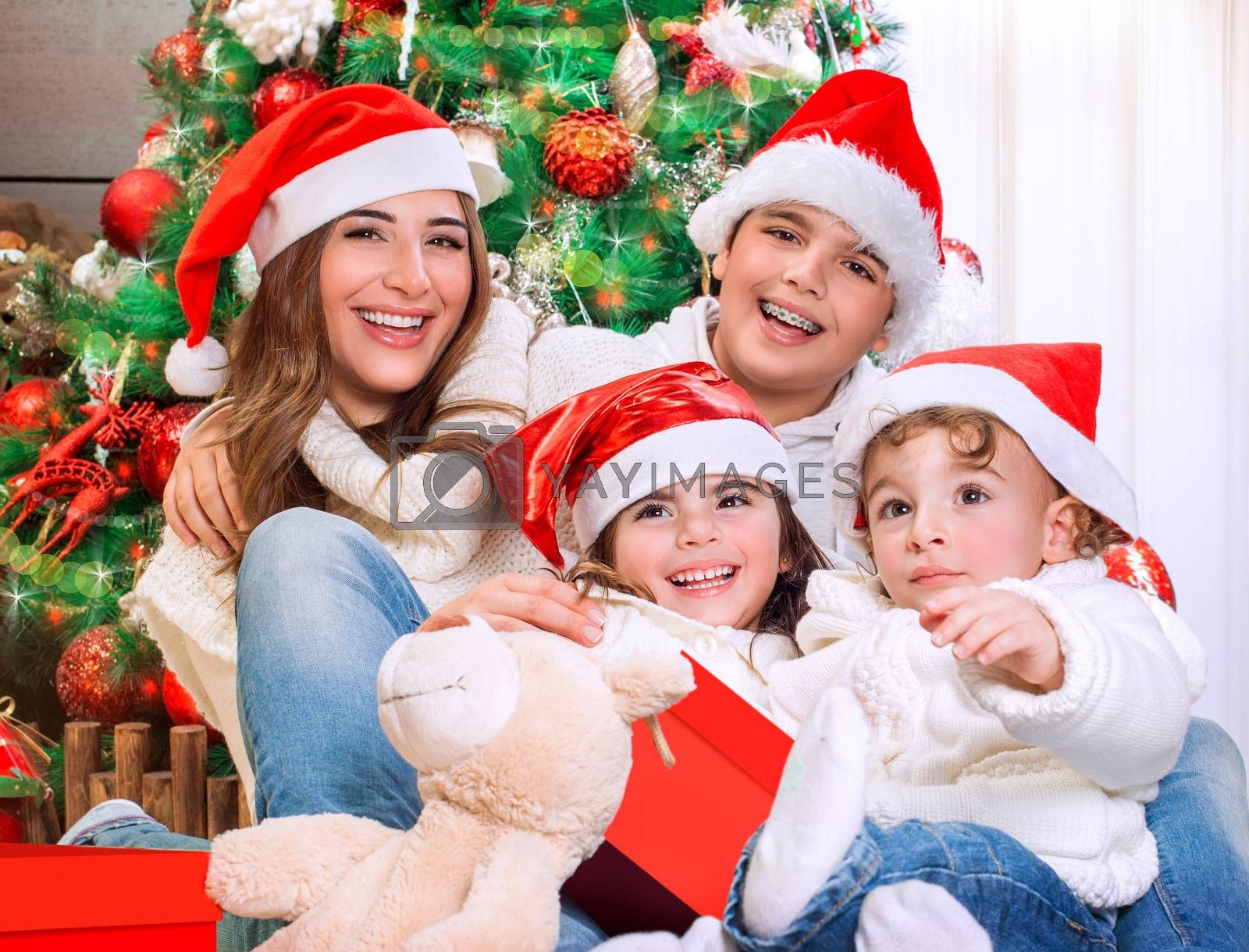 Portrait of big happy family in Xmas eve sitting under festive decorated Christmas tree, celebrating holidays at home