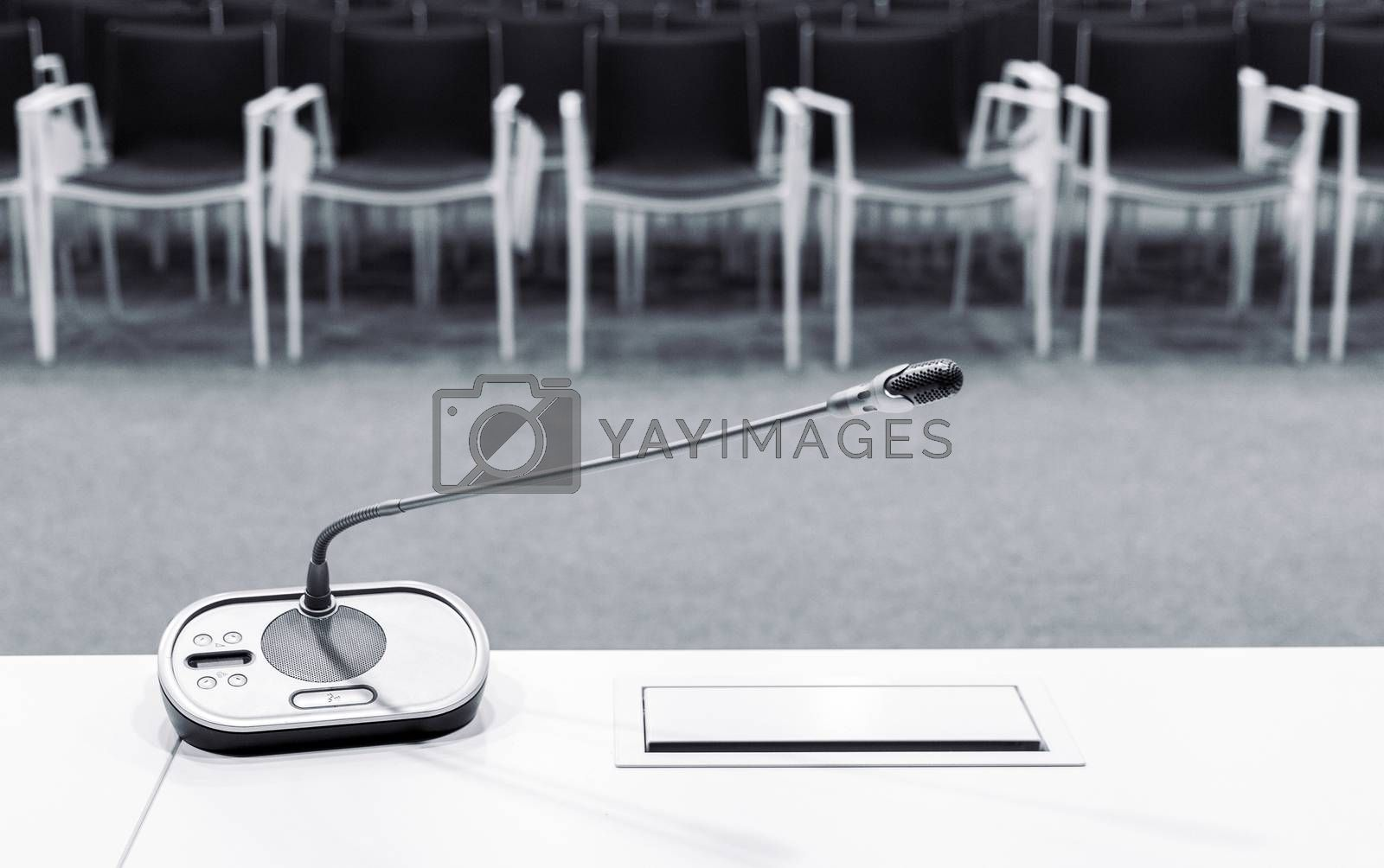 Microphone in press conference room with empty seats in the background