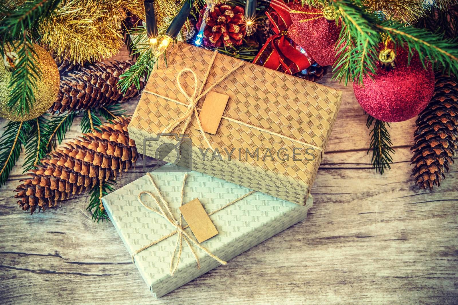 Overhead retro shot on cartons decorated with string and label on a wooden table under Christmas tree with cones