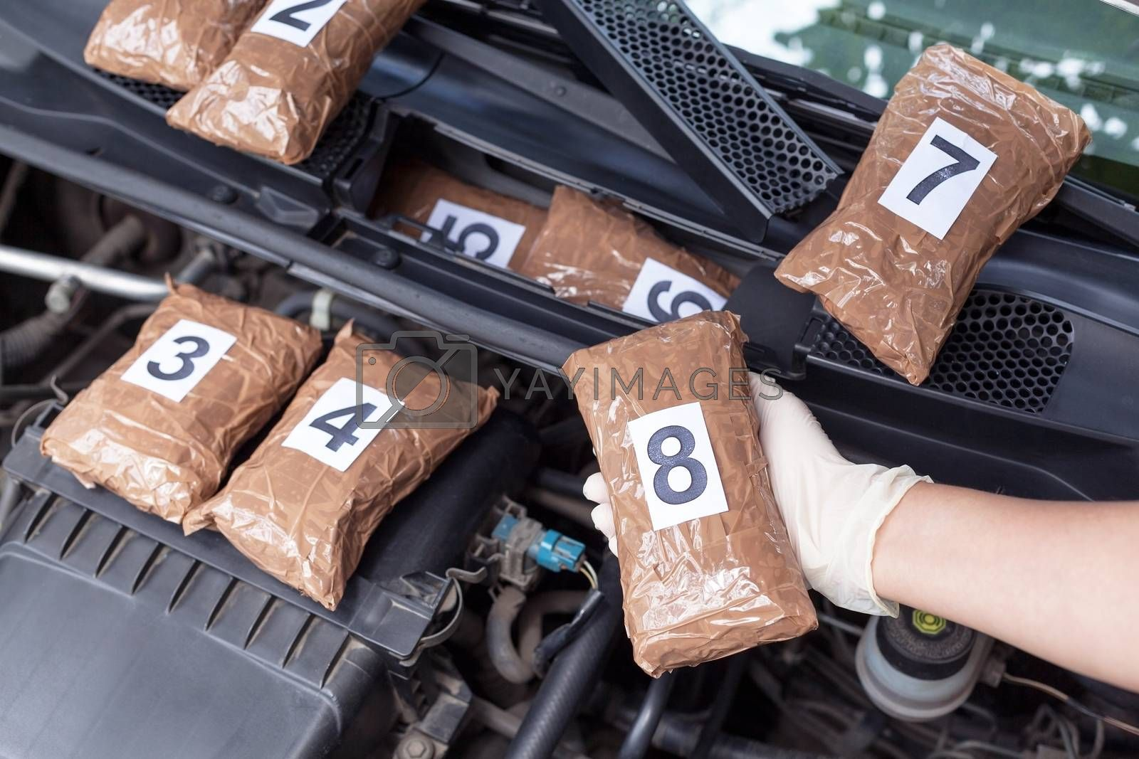 Police officer holding drug package discovered in engine compartment of a car