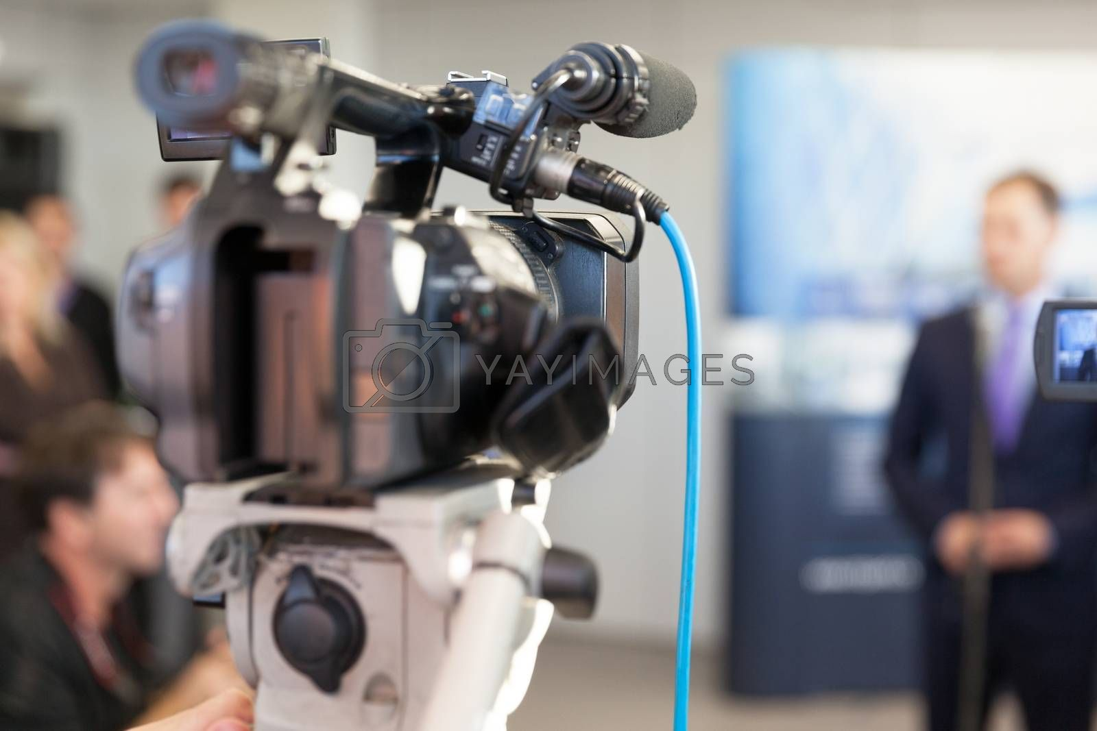 Video camera in focus, blurred spokesman in background. Corporate news conference.