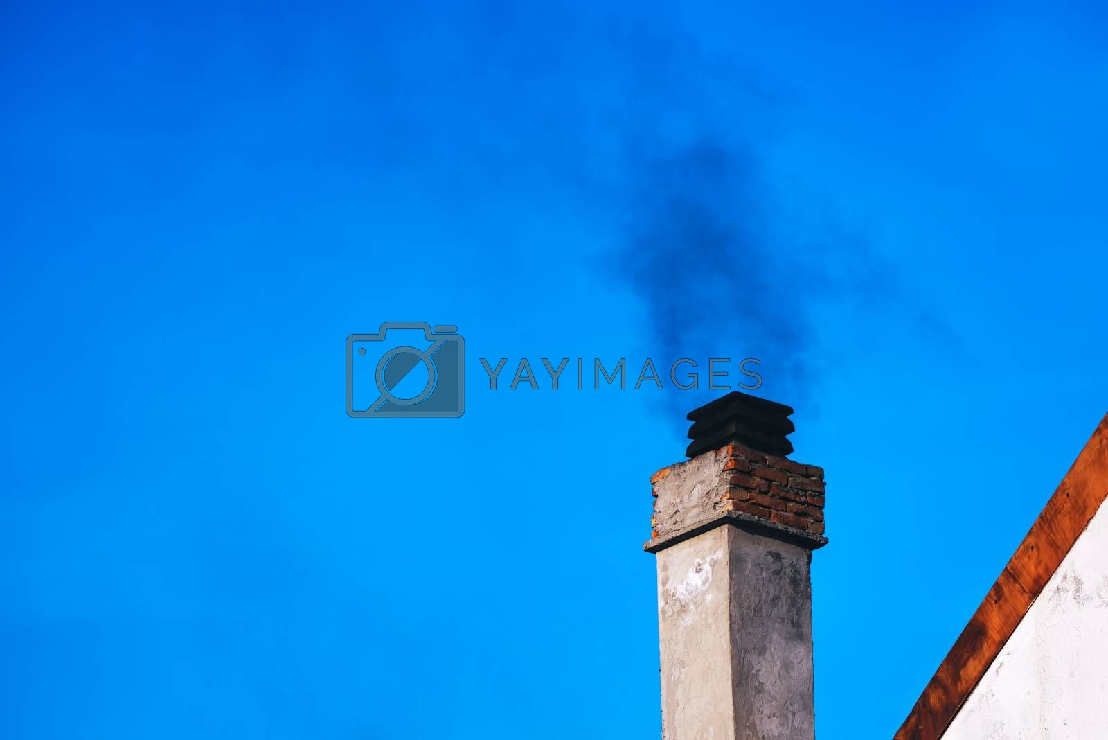 Smoke from house chimney on winter day