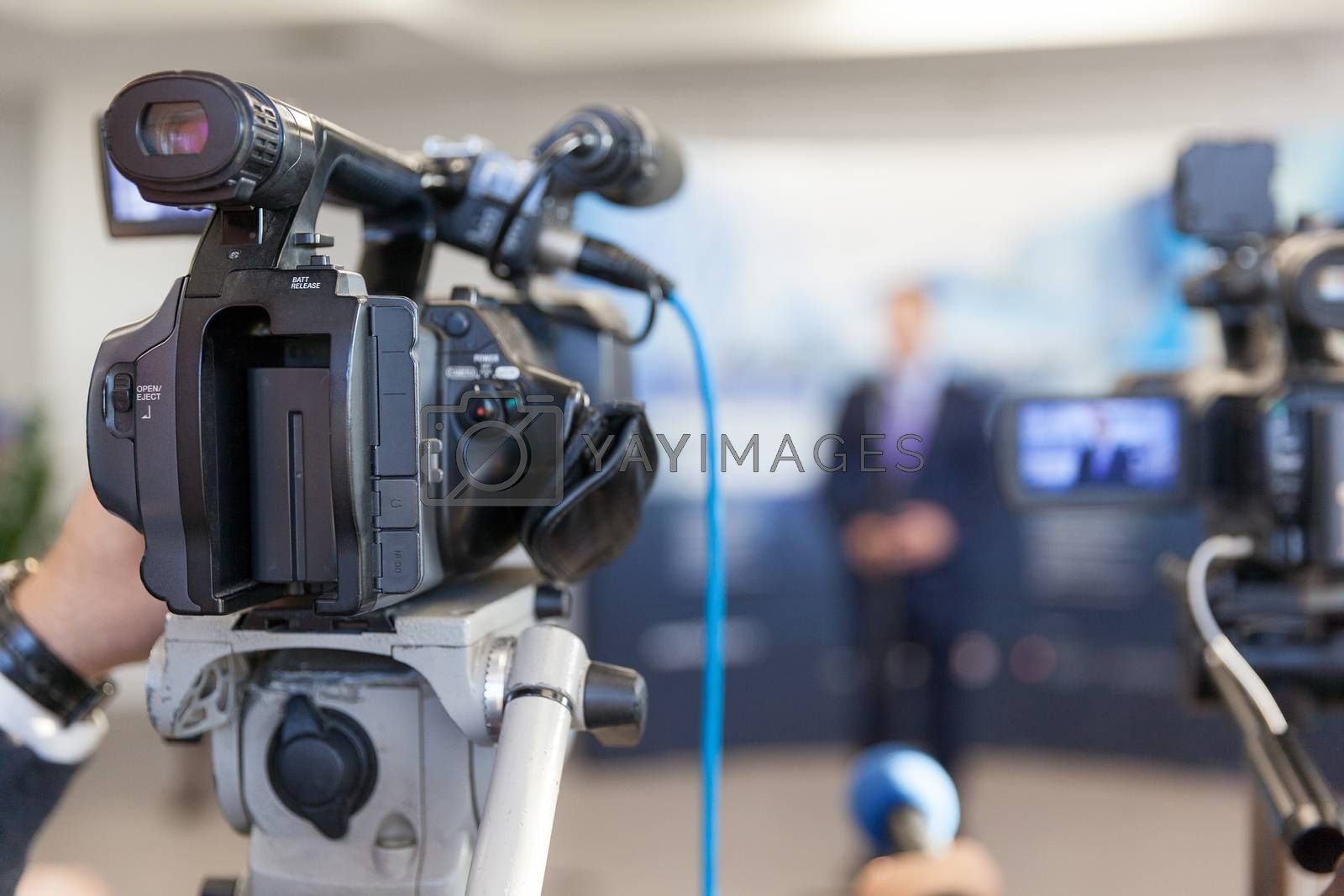 Video camera in focus, blurred spokesperson in background. Corporate news conference.
