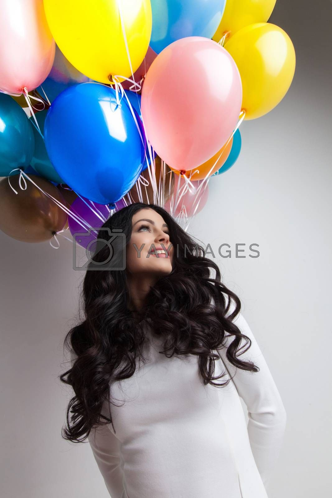 Cheerful woman holding many colorful balloons, celebration and happiness concept