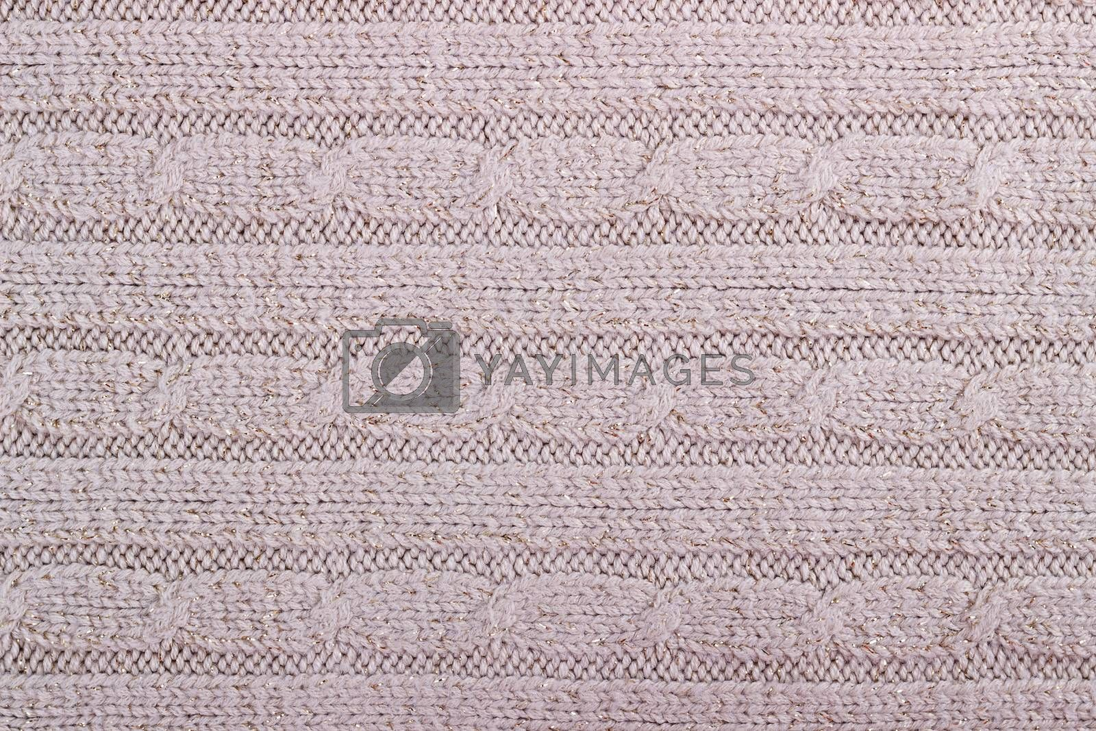 Texture of beige knitted woolen fabric for wallpaper and an abstract background