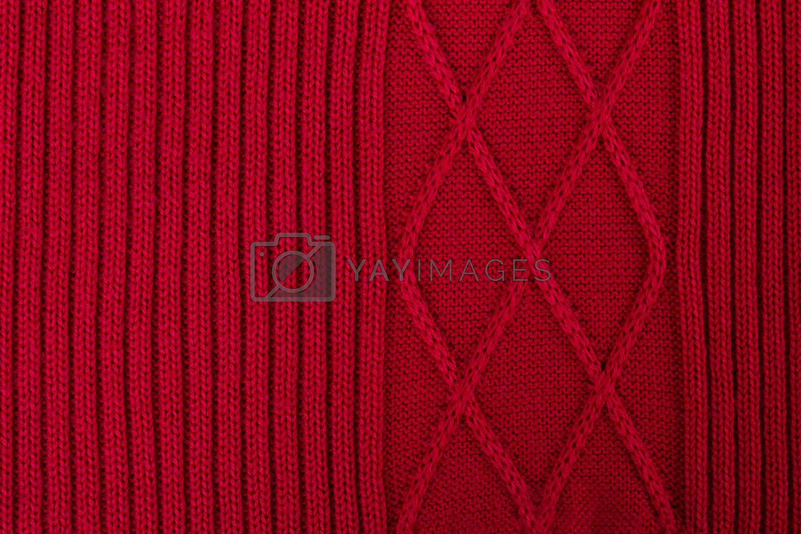 Texture of red knitted woolen fabric for wallpaper and an abstract background